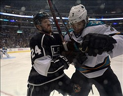 May 23, 2013; Los Angeles, CA, USA; Los Angeles Kings center Coliln Fraser (24) checks San Jose Sharks defenseman Brad Stuart (7) into the boards in game five of the second round of the 2013 Stanley Cup Playoffs at the Staples Center. The Kings defeated the Sharks to take a 3-2 series lead. Mandatory Credit: Kirby Lee-USA TODAY Sports