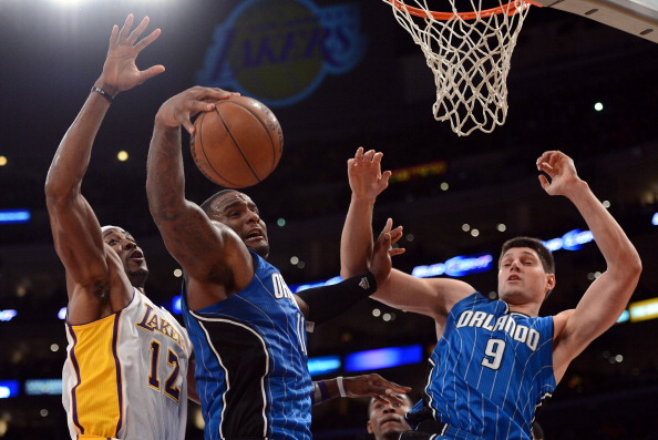 LOS ANGELES, CA - DECEMBER 02:  Glen Davis #11 of the Orlando Magic grabs a rebound from Dwight Howard #12 of the Los Angeles Lakers in front of teammate Nikola Vucevic #9 at Staples Center on December 2, 2012 in Los Angeles, California.  NOTE TO USER: User expressly acknowledges and agrees that, by downloading and or using this photograph, User is consenting to the terms and conditions of the Getty Images License Agreement.  (Photo by Harry How/Getty Images)