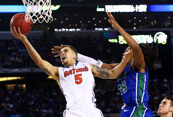 ARLINGTON, TX - MARCH 29:  Scottie Wilbekin #5 of the Florida Gators goes up against Sherwood Brown #25 of the Florida Gulf Coast Eagles during the South Regional Semifinal round of the 2013 NCAA Men's Basketball Tournament at Dallas Cowboys Stadium on March 29, 2013 in Arlington, Texas.  (Photo by Ronald Martinez/Getty Images)