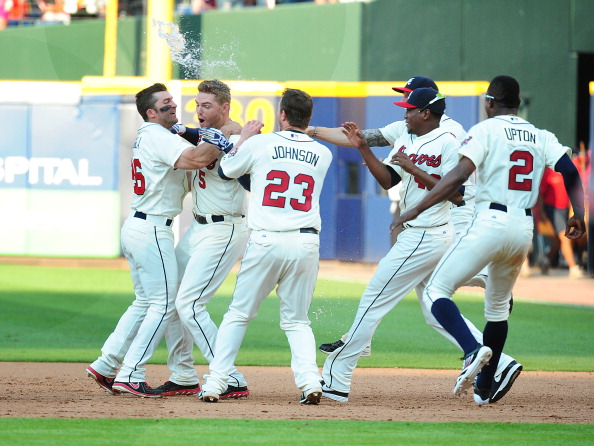 ATLANTA, GA - JUNE 15: Freddie Freeman #5 of the Atlanta Braves is mobbed by teammates after knocking in the game-winning run in the ninth inning against the San Francisco Giants at Turner Field on June 15, 2013 in Atlanta, Georgia. (Photo by Scott Cunningham/Getty Images)
