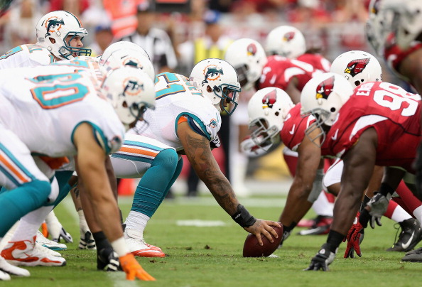 GLENDALE, AZ - SEPTEMBER 30:  Center Mike Pouncey #51 of the Miami Dolphins prepares to snap the football to quarterback Ryan Tannehill #17 during the NFL game against the Arizona Cardinals at the University of Phoenix Stadium on September 30, 2012 in Glendale, Arizona.  (Photo by Christian Petersen/Getty Images)