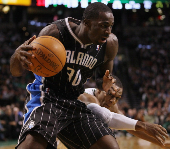 BOSTON, MA - JANUARY 17:   Brandon Bass #30 of the Orlando Magic tries to keep the ball as Rajon Rondo #9 of the Boston Celtics defends on January 17, 2011 at the TD Garden in Boston, Massachusetts. The Celtics defeated the Magic 109-106.  NOTE TO USER: User expressly acknowledges and agrees that, by downloading and/or using this Photograph, User is consenting to the terms and conditions of the Getty Images License Agreement.  (Photo by Elsa/Getty Images)