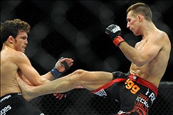 Jul 27, 2013; Seattle, WA, USA;  Rory MacDonald (red tape) lands a kick to the mid-section of Jake Ellenberger (blue tape) during their welterweight bout at Key Arena. McDonald won by a decision. Mandatory Credit: Jayne Kamin-Oncea-USA TODAY Sports