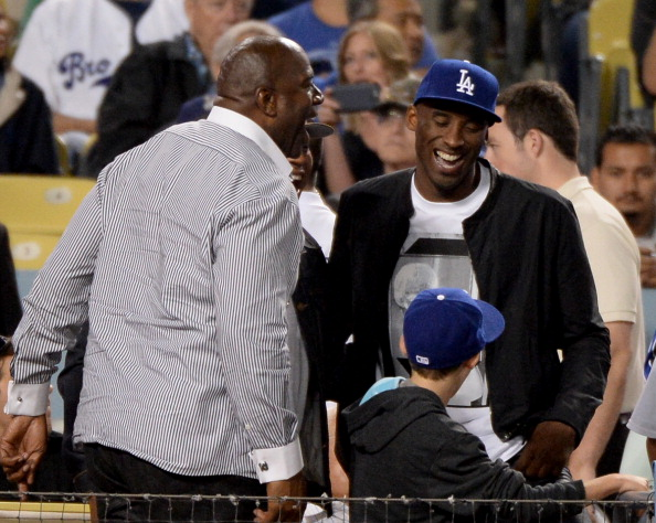 LOS ANGELES, CA - JULY 31:  Kobe Bryant of the Los Angeles Lakers and Magic Johnson laugh during the game against the New York Yankees at Dodger Stadium on July 31, 2013 in Los Angeles, California.  (Photo by Harry How/Getty Images)
