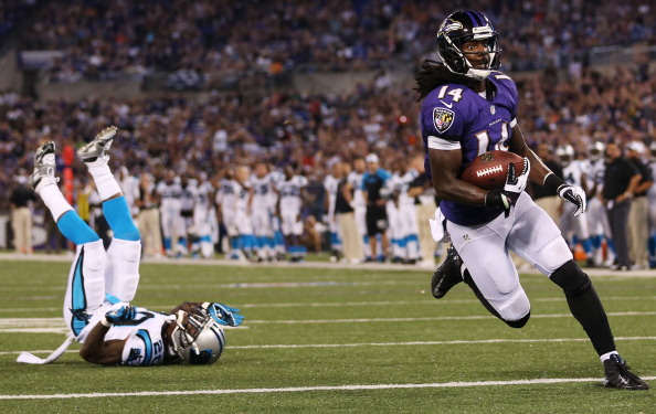 BALTIMORE, MD - AUGUST 22: Wide receiver Marlon Brown #14 of the Baltimore Ravens scores a touchdown after catching a pass in front of cornerback D.J. Moore #20 of the Carolina Panthers  during the second half of a preseason game at M&T Bank Stadium on August 22, 2013 in Baltimore, Maryland.  (Photo by Rob Carr/Getty Images)