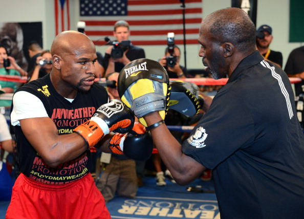 LAS VEGAS, NV - AUGUST 28:  Boxer Floyd Mayweather Jr. (L) works out with his trainer and uncle Roger Mayweather at the Mayweather Boxing Club on August 28, 2013 in Las Vegas, Nevada. Mayweather will face Canelo Alvarez in a WBC/WBA 154-pound title fight on September 14 in Las Vegas.  (Photo by Ethan Miller/Getty Images)