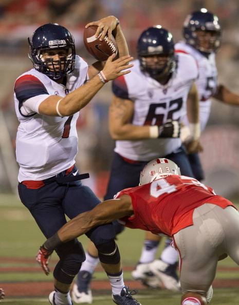 LAS VEGAS, NV - SEPTEMBER 07:  Quarterback B.J. Denker #7 of the Arizona Wildcats tries to avoid being tackled by Tim Hasson #43 of the UNLV Rebels during their game at Sam Boyd Stadium on September 7, 2013 in Las Vegas, Nevada. Arizona won 58-13. (Photo by Ethan Miller/Getty Images)