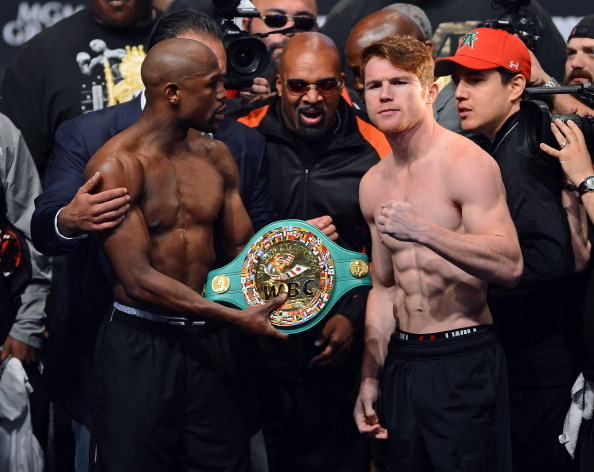 LAS VEGAS, NV - SEPTEMBER 13:  CEO of Mayweather Promotions Leonard Ellerbe (C) looks on as boxer Floyd Mayweather Jr. (L) tries to get boxer Canelo Alvarez (R) to hold a WBC belt as they pose during the official weigh-in for their bout at the MGM Grand Garden Arena on September 13, 2013 in Las Vegas, Nevada. The fighters will meet in a WBC/WBA 154-pound title fight on September 14 in Las Vegas.  (Photo by Ethan Miller/Getty Images)
