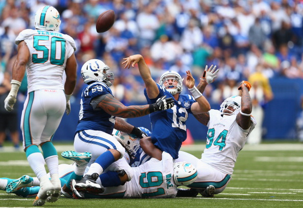 INDIANAPOLIS, IN - SEPTEMBER 15:  Andrew Luck #12 of the Indianapolis Colts throws the ball while being sacked on 4th down late in the 4th quarter 03 the 24-20 loss to the  Miami Dolphins at Lucas Oil Stadium on September 15, 2013 in Indianapolis, Indiana.  (Photo by Andy Lyons/Getty Images)