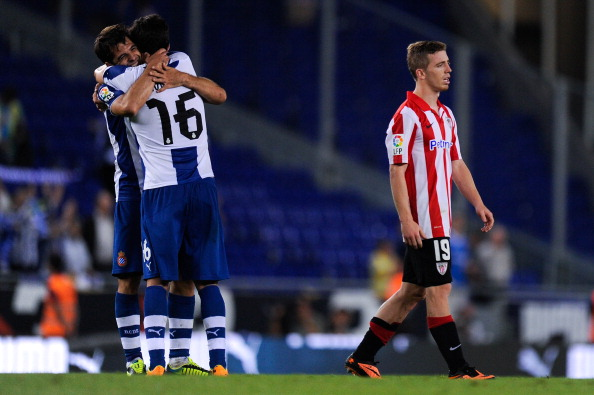 BARCELONA, SPAIN - SEPTEMBER 23: Iker Muniain (R) of Athletic Club leaves the pitch dejected after being defeated as Victor Sanchez of RCD Espanyol and his team-mate Javi Lopez of RCD Espanyol celebrate their victory during the La Liga match between RCD Espanyol and Athletic Club at Cornella-El Prat Stadium on September 23, 2013 in Barcelona, Spain.  (Photo by David Ramos/Getty Images)