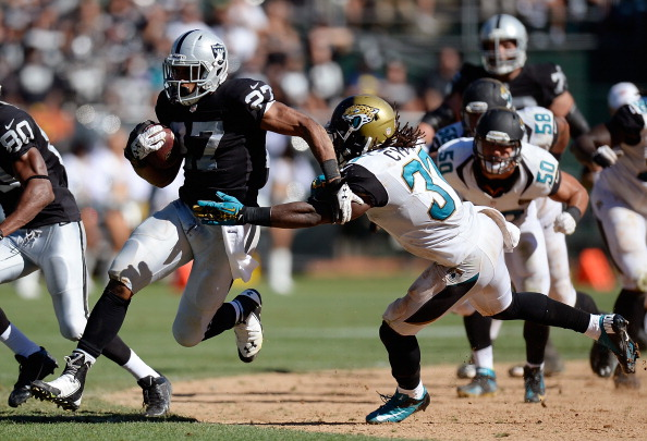 OAKLAND, CA - SEPTEMBER 15:  Rashad Jennings #27 of the Oakland Raiders rushes for twenty eight yards breaking the tackle of Johnathan Cyprien #37 of the Jacksonville Jaguars during the fourth quarter at O.co Coliseum on September 15, 2013 in Oakland, California. The Raiders won the game 19-9. (Photo by Thearon W. Henderson/Getty Images)