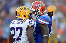 Oct 6, 2012; Gainesville, FL, USA; Florida Gators linebacker Lerentee McCray (34) and LSU Tigers running back Kenny Hilliard (27) exchange words during the fourth quarter at Ben Hill Griffin Stadium. Mandatory Credit: Jake Roth-USA TODAY Sports