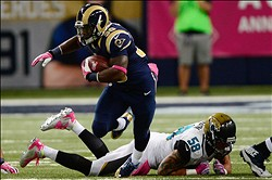 Oct 6, 2013; St. Louis, MO, USA; St. Louis Rams running back Zac Stacy (30) runs past Jacksonville Jaguars defensive end Jason Babin (58) during the first half at the Edward Jones Dome. Mandatory Credit: Jeff Curry-USA TODAY Sports