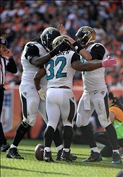 Oct 13, 2013; Denver, CO, USA; Jacksonville Jaguars running back Maurice Jones-Drew (32) is congratulated for his touchdown run by  guard Uche Nwaneri (77) and quarterback Chad Henne (7) in the third quarter against the Denver Broncos at Sports Authority Field at Mile High. Mandatory Credit: Ron Chenoy-USA TODAY Sports