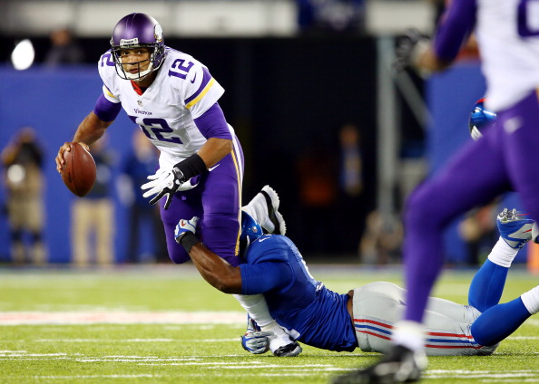 EAST RUTHERFORD, NJ - OCTOBER 21: Quarterback Josh Freeman #12 of the Minnesota Vikings is sacked by defensive end Justin Tuck #91 of the New York Giants during a game at MetLife Stadium on October 21, 2013 in East Rutherford, New Jersey.  (Photo by Elsa/Getty Images)