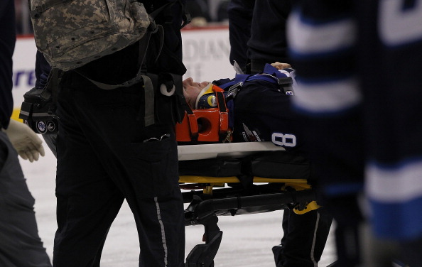 WINNIPEG, MB - OCTOBER 18:  Jacob Trouba #8 of the Winnipeg Jets is taken off the ice on a stretcher after he crashed into the boards in second-period action of an NHL game against the St. Louis Blues at the MTS Centre on October 18, 2013 in Winnipeg, Manitoba, Canada. (Photo by Marianne Helm/Getty Images)