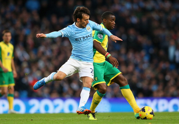 MANCHESTER, ENGLAND - NOVEMBER 02:  David Silva of Manchester City competes with Sebastien Bassong of Norwich during the Barclays Premier League match between Manchester City and Norwich City at Etihad Stadium on November 2, 2013 in Manchester, England.  (Photo by Alex Livesey/Getty Images)
