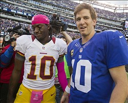 Oct 21, 2012; East Rutherford, NJ, USA; New York Giants quarterback Eli Manning (10) (right) meets Washington Redskins quarterback Robert Griffin III (10) (left)  after the New York Giants 27-23, come-from-behind win over the Washington Redskins at MetLife Stadium. Mandatory Credit: Andrew Mills/THE STAR-LEDGER via USA TODAY Sports