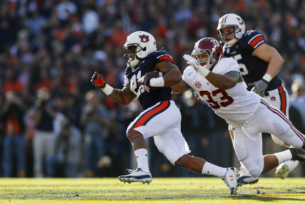 AUBURN, AL - NOVEMBER 30:  Tre Mason #21 of the Auburn Tigers tries to avoid the tackle of Trey DePriest #33 of the Alabama Crimson Tide in the first quarter at Jordan-Hare Stadium on November 30, 2013 in Auburn, Alabama.  (Photo by Kevin C. Cox/Getty Images)