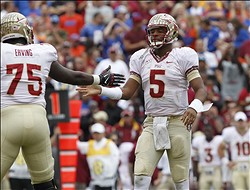 Nov 30, 2013; Gainesville, FL, USA; Florida State Seminoles quarterback Jameis Winston (5) high fives offensive linesman Cameron Erving (75) after they got first down on a penalty against the Florida Gators  during the first quarter at Ben Hill Griffin Stadium. Mandatory Credit: Kim Klement-USA TODAY Sports