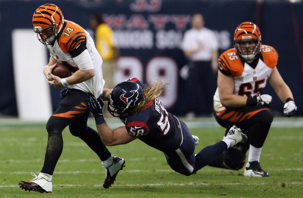 HOUSTON, TX - JANUARY 05:   Andy Dalton #14 of the Cincinnati Bengals is tackled by  Brooks Reed #58 of the Houston Texans during the AFC Wild Card Playoff Game at Reliant Stadium on January 5, 2013 in Houston, Texas.  (Photo by Ronald Martinez/Getty Images)