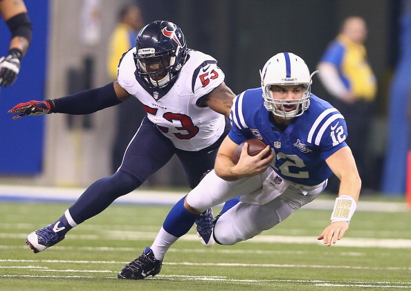 INDIANAPOLIS, IN - DECEMBER 15:  Andrew Luck #12 of the Indianapolis Colts runs with the ball while defended by Joe Mays #53 of the Houston Texans during the NFL game at Lucas Oil Stadium on December 15, 2013 in Indianapolis, Indiana.  (Photo by Andy Lyons/Getty Images)