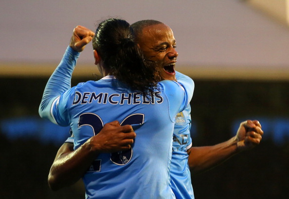 LONDON, ENGLAND - DECEMBER 21:  Vincent Kompany of Manchester City celebrates scoring their second goal with Martin Demichelis of Manchester City during the Barclays Premier League match between Fulham and Manchester City at Craven Cottage on December 21, 2013 in London, England.  (Photo by Clive Rose/Getty Images)