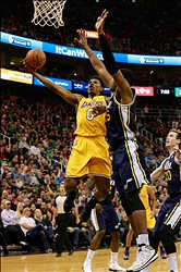Dec 27, 2013; Salt Lake City, UT, USA; Los Angeles Lakers small forward Nick Young (0) tries to shoot the ball past Utah Jazz power forward Derrick Favors (15) during the second quarter at EnergySolutions Arena. Mandatory Credit: Chris Nicoll-USA TODAY Sports