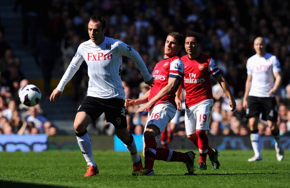LONDON, ENGLAND - APRIL 20:  Dimitar Berbatov of Fulham and Aaron Ramsey of Arsenal tussle for the ball during the Barclays Premier League match between Fulham and Arsenal at Craven Cottage on April 20, 2013 in London, England.  (Photo by Mike Hewitt/Getty Images)