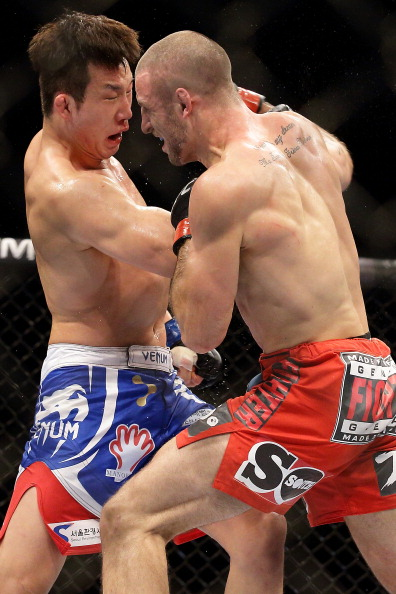 SINGAPORE - JANUARY 04:  Tarec Saffiedine (R) fights Lim Hyun Gyu during their UFC Fight Night Singapore welterweight bout at Marina Bay Sands on January 4, 2014 in Singapore.  (Photo by Suhaimi Abdullah/Getty Images)