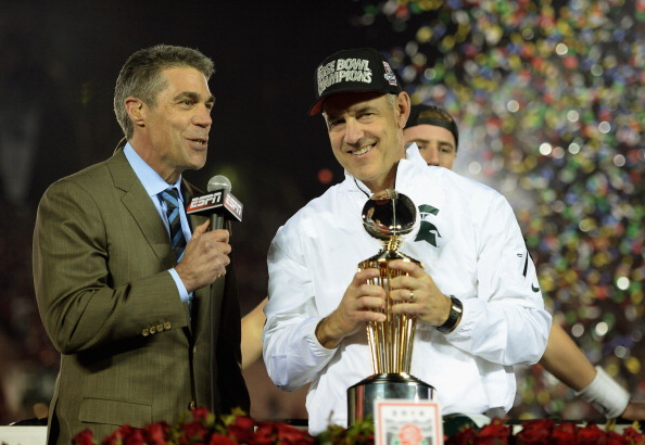PASADENA, CA - JANUARY 01:  Michigan State Spartans head coach Mark Dantonio is presented the Rose Bowl Game trophy by ESPN's Chris Fowler after defeating the Stanford Cardinal 24-20 in the 100th Rose Bowl Game presented by Vizio at the Rose Bowl on January 1, 2014 in Pasadena, California.  (Photo by Harry How/Getty Images)