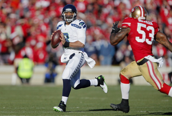 SAN FRANCISCO, CA - DECEMBER 08:  Quarterback Russell Wilson #3 of the Seattle Seahawks looks for a receiver against linebacker NaVorro Bowman #53 of the San Francisco 49ers in the second quarter on December 8, 2013 at Candlestick Park in San Francisco, California.  The 49ers won 19-17.  (Photo by Brian Bahr/Getty Images)