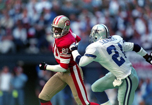 12 Nov 1995: Jerry Rice #80 of the San Francisco 49ers runs with the ball as Deion Sanders #21 of the Dallas Cowboys runs after him during the game at the Texas Stadium in Irving, Texas. The 49ers defeated the Cowboys 38-20.