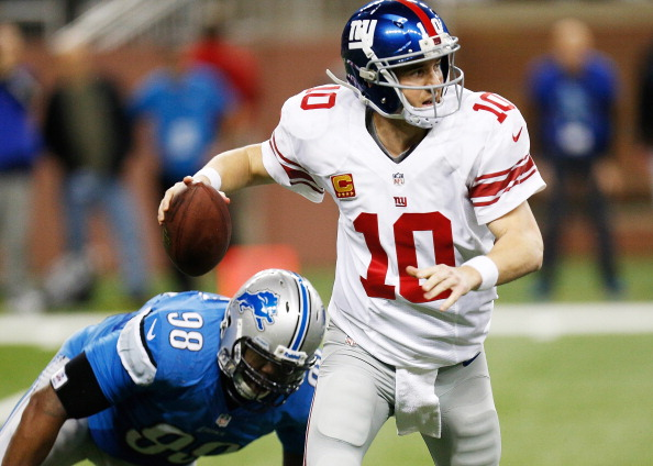 DETROIT, MI - DECEMBER 22: Eli Manning #10 of the New York Giants escapes the rush of Nick Fairley #98 of the Detroit Lions during the fourth quarter at Ford Field on December 22, 2013 in Detroit, Michigan. New York won the game in overtime 23-20. (Photo by Gregory Shamus/Getty Images)