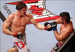 Nov 17, 2012; Montreal, QC, Canada; Matthew Riddle (left) punches John Maguire during their Welterweight bout at UFC 154 at the Bell Centre. Mandatory Credit: Tom Szczerbowski-USA TODAY Sports