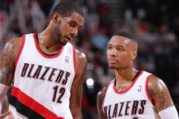 PORTLAND, OR - JANUARY 28:  LaMarcus Aldridge #12 and Damian Lillard #0 of the Portland Trail Blazers talk against the Memphis Grizzlies on January 28, 2014 at the Moda Center Arena in Portland, Oregon. NOTE TO USER: User expressly acknowledges and agrees that, by downloading and or using this photograph, user is consenting to the terms and conditions of the Getty Images License Agreement. Mandatory Copyright Notice: Copyright 2014 NBAE (Photo by Sam Forencich/NBAE via Getty Images)