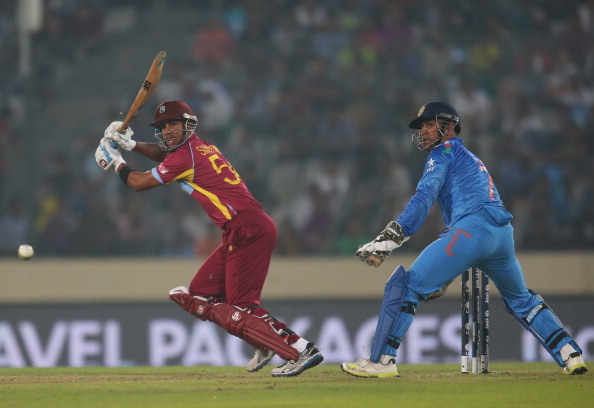 DHAKA, BANGLADESH - MARCH 23:  Lendl Simmons of the West Indies bats as MS Dhoni of India looks on during the ICC World Twenty20 Bangladesh 2014 match between the West Indies and India at Sher-e-Bangla Mirpur Stadium on March 23, 2014 in Dhaka, Bangladesh.  (Photo by Scott Barbour/Getty Images)