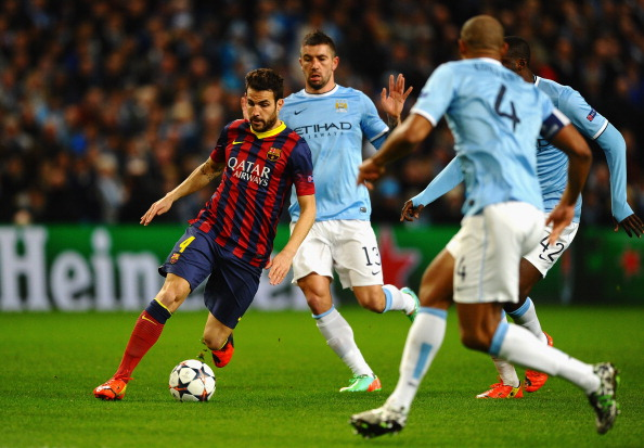 MANCHESTER, ENGLAND - FEBRUARY 18:  Cesc Fabregas of Barcelona competes with Aleksandar Kolarov of Manchester City during the UEFA Champions League Round of 16 first leg match between Manchester City and Barcelona at the Etihad Stadium on February 18, 2014 in Manchester, England.  (Photo by Laurence Griffiths/Getty Images)