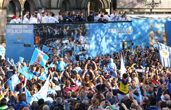 MANCHESTER, ENGLAND - MAY 12:  Vincent Kompany of Manchester City lifts the Barclays Premier League trophy aloft outside Manchester Town Hall at the start of the Manchester City victory parade around the streets of Manchester on May 12, 2014 in Manchester, England.  (Photo by Alex Livesey/Getty Images)