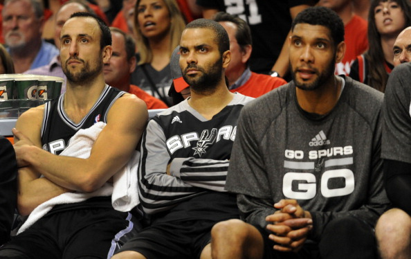 PORTLAND, OR - MAY 12: Manu Ginobili #20, Tony Parker #9 and Tim Duncan #21 of the San Antonio Spurs watch from the bench in the fourth quarter of Game Four of the Western Conference Semifinals during the 2014 NBA Playoffs at the Moda Center on May 12, 2014 in Portland, Oregon. The Blazers won the game 103-92. NOTE TO USER: User expressly acknowledges and agrees that, by downloading and or using this photograph, User is consenting to the terms and conditions of the Getty Images License Agreement. (Photo by Steve Dykes/Getty Images)
