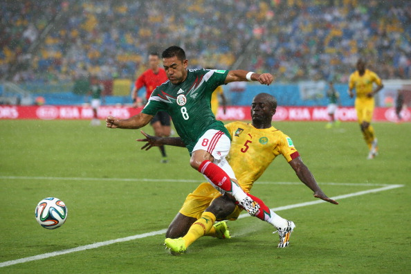 NATAL, BRAZIL - JUNE 13: Marco Fabian of Mexico is tackled by Dany Nounkeu of Cameroon during the 2014 FIFA World Cup Brazil Group A match between Mexico and Cameroon at Estadio das Dunas on June 13, 2014 in Natal, Brazil.  (Photo by Julian Finney/Getty Images)