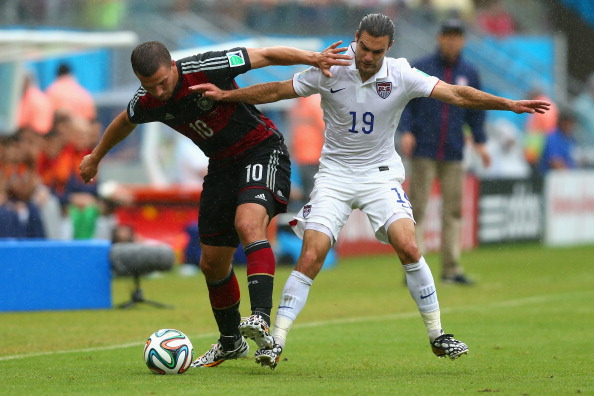 RECIFE, BRAZIL - JUNE 26: Lukas Podolski of Germany is challenged by Graham Zusi of the United States during the 2014 FIFA World Cup Brazil group G match between the United States and Germany at Arena Pernambuco on June 26, 2014 in Recife, Brazil.  (Photo by Martin Rose/Getty Images)