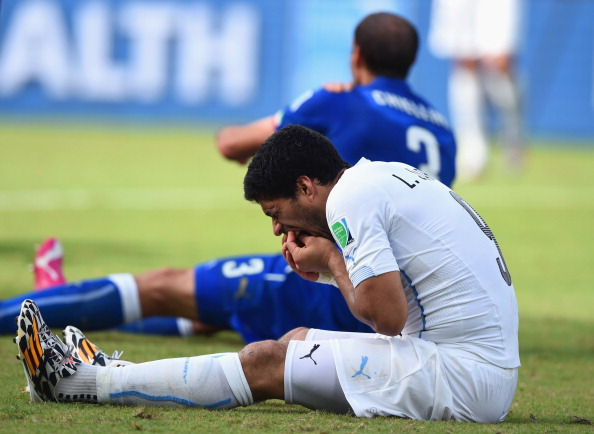 NATAL, BRAZIL - JUNE 24:  Luis Suarez of Uruguay and Giorgio Chiellini of Italy react after a clash during the 2014 FIFA World Cup Brazil Group D match between Italy and Uruguay at Estadio das Dunas on June 24, 2014 in Natal, Brazil.  (Photo by Matthias Hangst/Getty Images)
