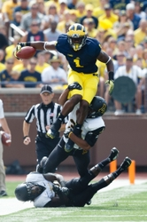 Aug 30, 2014; Ann Arbor, MI, USA; Michigan Wolverines wide receiver Devin Funchess (87) leaps over Appalachian State Mountaineers defensive back Dante Blackmon (24) as linebacker Rashaad Townes (31) grabs him from behind in the first quarter at Michigan Stadium. Mandatory Credit: Rick Osentoski-USA TODAY Sports