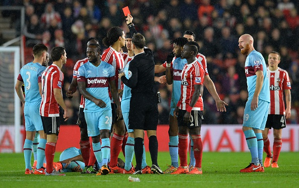 Referee Mark Clattenburg (C) shows Southampton's Kenyan midfielder Victor Wanyama (3L) the red card for a challenge on West Ham United's French midfielder Dimitri Payet (laying on pitch) during the English Premier League football match between Southampton and West Ham United at St Mary's Stadium in Southampton, southern England on February 6, 2016. / AFP / GLYN KIRK / RESTRICTED TO EDITORIAL USE. No use with unauthorized audio, video, data, fixture lists, club/league logos or 'live' services. Online in-match use limited to 75 images, no video emulation. No use in betting, games or single club/league/player publications.  /         (Photo credit should read GLYN KIRK/AFP/Getty Images)