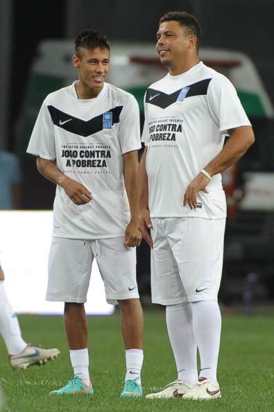 Brazilian football player Ronaldo (R) and Neymar speak before their 'Match Against Poverty' friendly football match led by the United Nations Development Programme (UNDP), between the teams 'Friends of Ronaldo' and 'Friends of Zidane' in southern Brazil's Porto Alegre on December 19, 2012.  AFP PHOTO / Yasuyoshi CHIBA        (Photo credit should read YASUYOSHI CHIBA/AFP/Getty Images)
