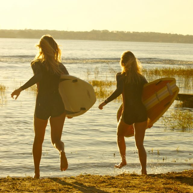 Surfer Girls heading out to Four Winns boat on Lake Hawaii