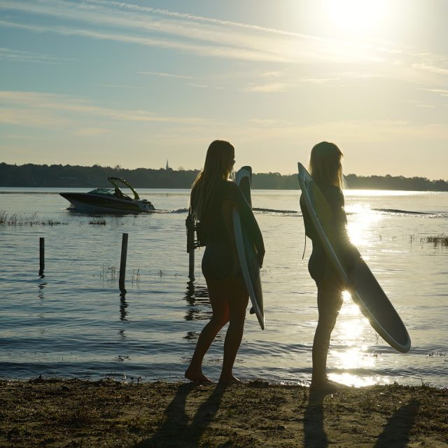 Surfer girls waiting to go out to Four Winns TS 222 Wakesurf Boat on Lake Hawaii