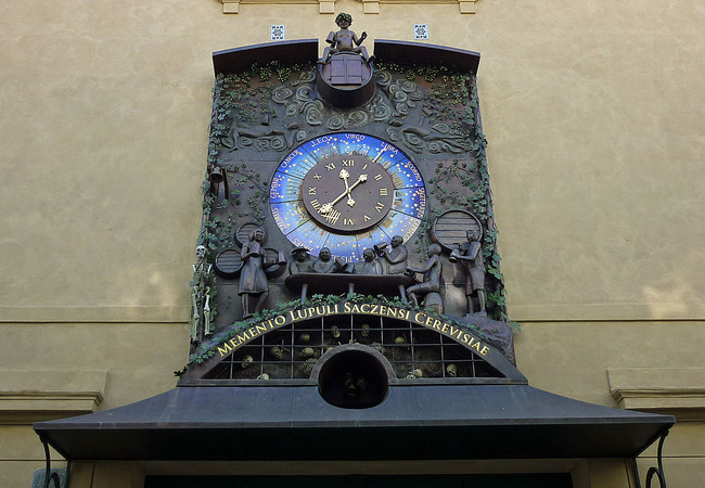 Clock with people drinking at a bar while a cemetery is embedded below, in Žatec, Czech Republic (photograph by SchiDD/Wikimedia)