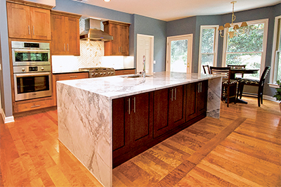 Warm tones of blue accent the earthy wood tones in this Lowcountry kitchen. DISTINCTIVE GRANITE AND MARBLE